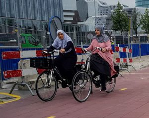 Two women cycle and chat together in Utrecht.
