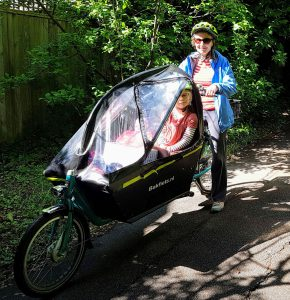 A mother with a bakfiets cargo bike and her daughter on-board.