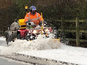 Quad bike removing snow from a cycle lane