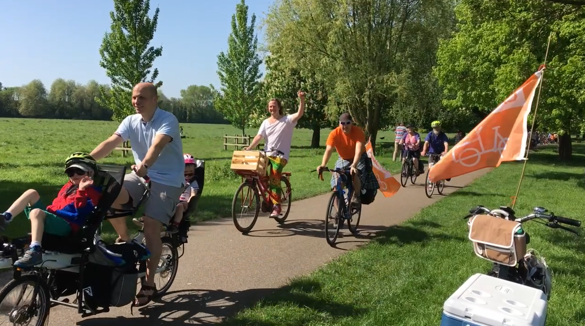A number of people riding through Stourbridge Common including a father on a tandem cycle with two children