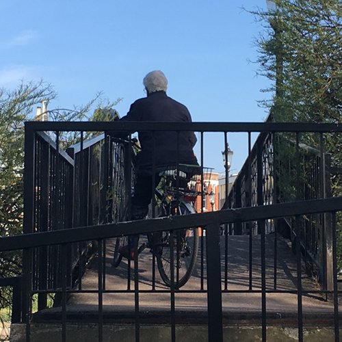 Cyclist riding over Jesus Lock bridge